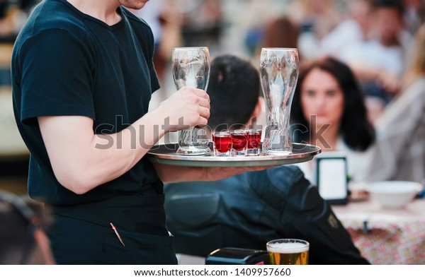 Waiter with tray takes empty beer glasses and brings cocktails to the guests of restaurant on the summer terrace. Service in cafes and restaurants. Man holding the tray with red cocktails