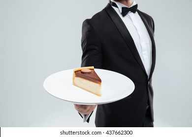 Waiter in tuxedo with bowtie holding plate with piece of cake