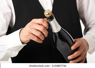 Waiter uncorking a bottle of champagne