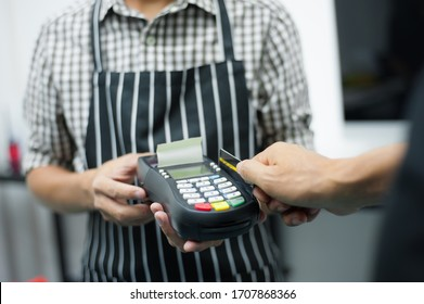 The waiter uses a card reader for customers using credit cards.
