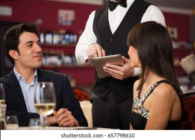 Waiter using a tablet to take an order