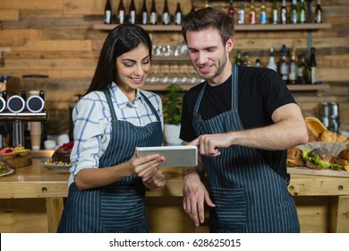 Waiter and waitresses using digital tablet at counter in cafe