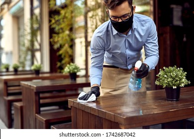 Photo of Waiter wearing protective face mask while disinfecting tables at outdoor cafe.