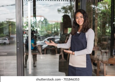 waiter welcoming customer to come to her newly open cafe