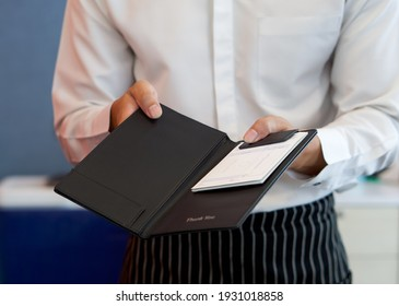 The waiter in a white shirt and apron presents a receipt after calling the bill.