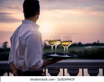 Waiter in white shirt holding tray of four wine glasses looking at sunset and golf course