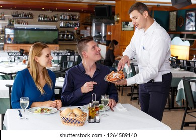 Waiter in white shirt serving delicious dishes to couple at restaurant