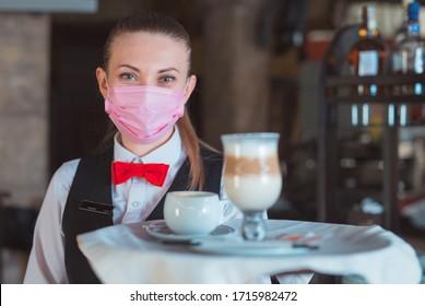 der Kellner arbeitet in einem Restaurant in einer medizinischen Maske