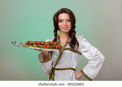 Waiters carrying plates with meat on green background