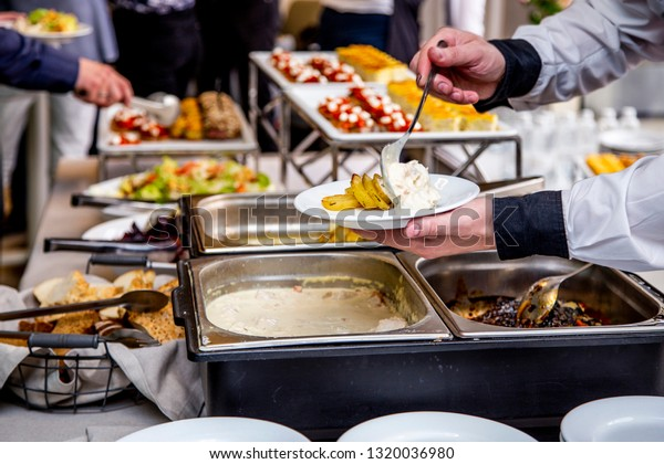 waiter's hands are putting potatoes and chicken meat in a sauce on a plate at catering event on some festive event, party or wedding reception