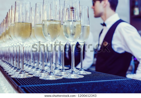 Waiters in uniform serving champagne