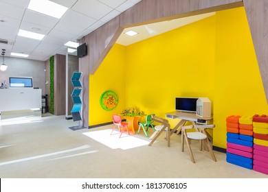Der Wartebereich mit Spielplatz für Kinder. Hellgelber Spielplatz mit kleinen, bunten Möbeln und Spielzeug für kleine Kinder
