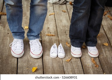 Waiting of baby. Little white baby's bootees near mom's and dad's. Pregnant woman, pregnancy, motherhood. Happy family. Mom's, Dad's and baby's bootees. Family look