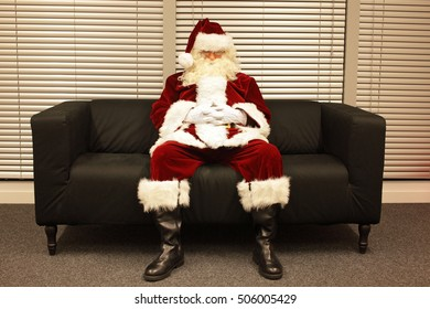 waiting for christmas job, santa claus sleeping on sofa in office