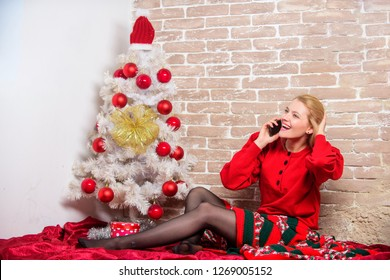 Waiting for christmas. Voicemail greeting. Woman cheerful hold smartphone enjoy mobile phone conversation. Girl in dress sit near christmas tree with ornaments. Wishing everyone merry xmas .