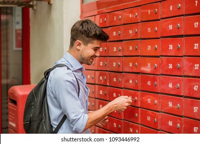Waiting for delivery. Young man, smart casual, at the mailboxes post, checking the mail