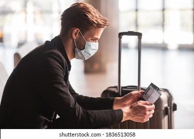 Warten auf einen Flug. Ein Mann, der eine Gesichtsmaske trägt, während er auf einen Flug wartet