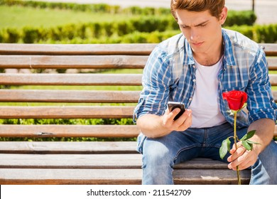 Waiting for his girlfriend. Worried young man holding single rose and looking at his mobile phone while sitting on the bench