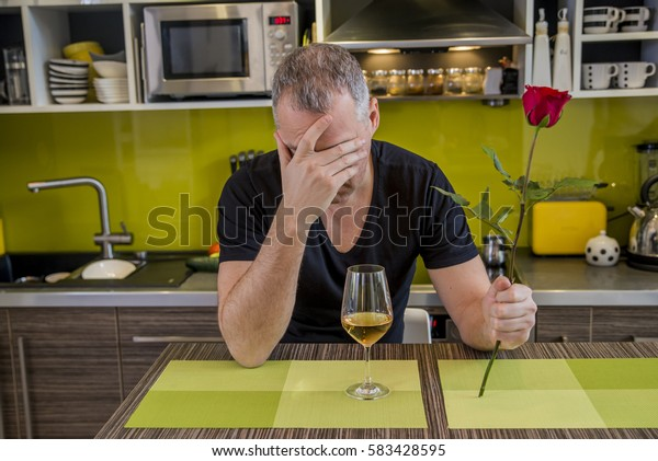Waiting for his girlfriend. Worried young man holding single rose and looking depressed while sitting in the kitchen