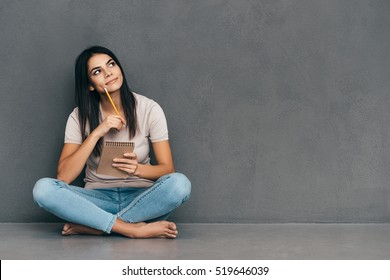 Waiting for inspiration. Attractive young woman in casual wear holding notebook and pen while sitting barefoot and against grey background
