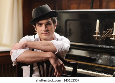 Waiting for inspiration. Portrait of handsome young men sitting in front of his piano