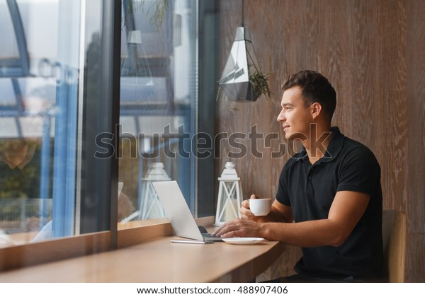 Waiting for inspiration. Thoughtful young man holding coffee cup and looking away while sitting at cafe near large window