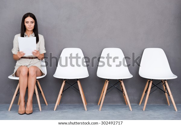 Waiting for interview. Confident young businesswoman holding paper while sitting on chair against grey background