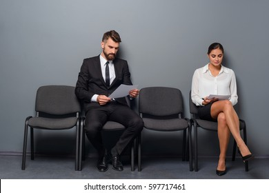 Waiting for an interview. Two unemployed people are sitting on chairs and checking their resumes before they go to HR-specialist. A gray wall in the background.