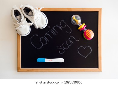 """Waiting for labour, maternity concept. """"Coming soon"""" words on black chalkboard with positive pregnancy test, white baby shoes and rattle"""