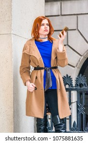 Waiting phone call. Young American businesswoman, wearing long brown woolen overcoat, blue undershirt, standing by metal railing outside office building, holding cell phone, thinking, lost in thought.