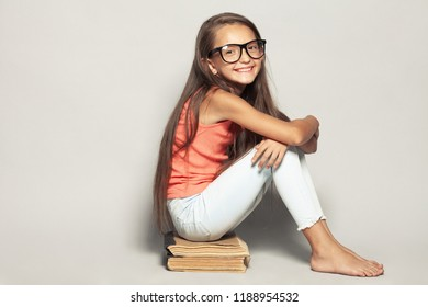 Waiting for the rest concept. Portrait of a happy funny girl after sitting on manuels over light gray background in summer season casual clothing. Copy-space. Studio shot