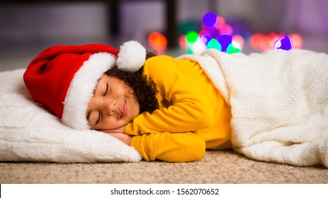 Waiting for Santa Claus. Adorable little african american little girl sleeping on floor on Christmas night, panorama