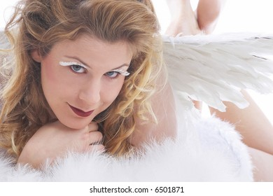 waiting for snowflakes, woman in white angel costume with big wings looks to heaven