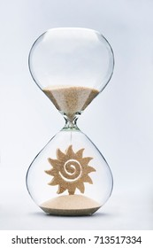 Waiting for the summer concept with falling sand taking the shape of the sun inside a hourglass