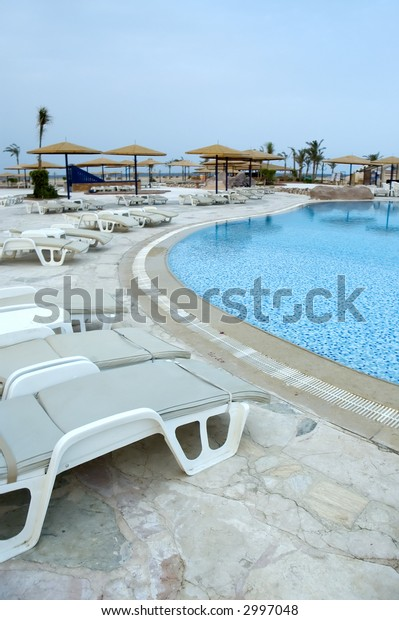 Waiting for tourists - pool chairs at a resort pool in a morning