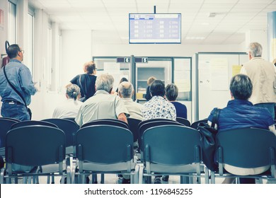 Waiting The Turn In A Hospital. Back View Of Sitting Group Of People