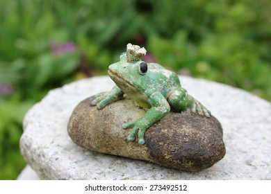 Waiting weathered stone frog statue waiting on a stone to be kissed in the garden, seen from birds eyes view looking up. Character from a Russian fairytale. Black eyes. Blurry green background.