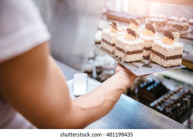 Waitress arranging cake at display cabinet in Confectionery Shop
