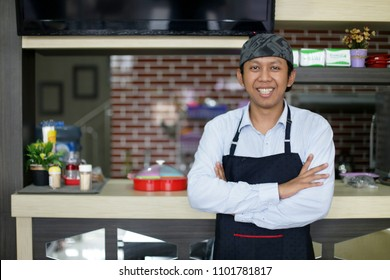 waitress asian man smiling. asian man smiling waitress standing with arms crossed in cafe. yogyakarta indonesia. may 31, 2018