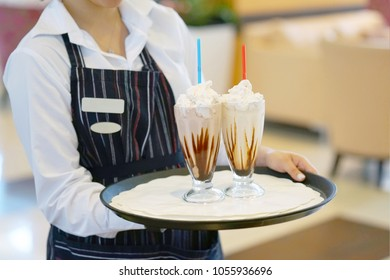 A waitress bears two vanilla milkshakes for the client of the hotel restaurant. Two chocolate dairy cocktails on a waitress tray.