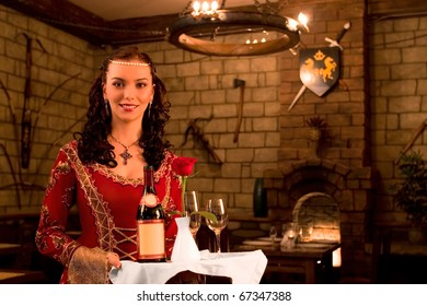 The waitress with black curly hair submits wine in the medieval castle
