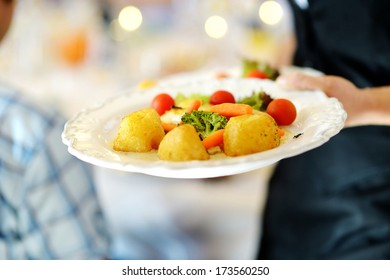 Waitress carrying a plate with vegetable dish