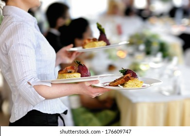 Waitress carrying three plates with meat dish