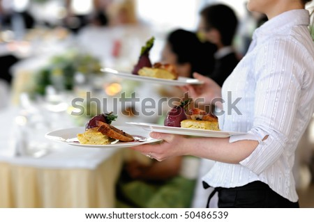 Waitress is carrying three plates with meat dish