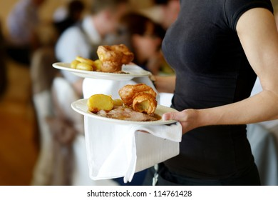 Waitress is carrying two plates with meat dish