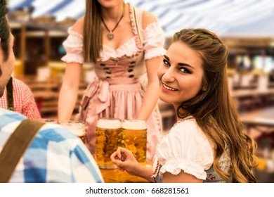 Waitress delivers beers with happy guests in a beer tent at Munich Oktoberfest