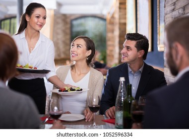 Waitress with dishes serving man and female friendly company indoors