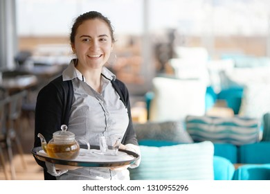 The waitress gives a cup of tea and tea glass teapot to a client in the hotel restaurant. The concept of service and maintenance