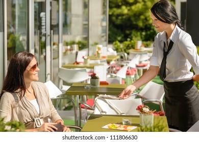 Waitress giving back to woman change money bill restaurant terrace