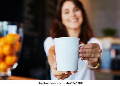 Waitress giving mug with coffee or tea